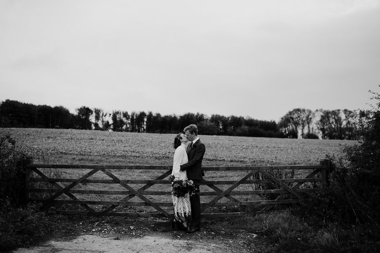 Black and White Portrait of Bride in Crochet Wedding Dress and Woollen Jumper with Her  Groom in Navy Suit Standing by a Field Fence