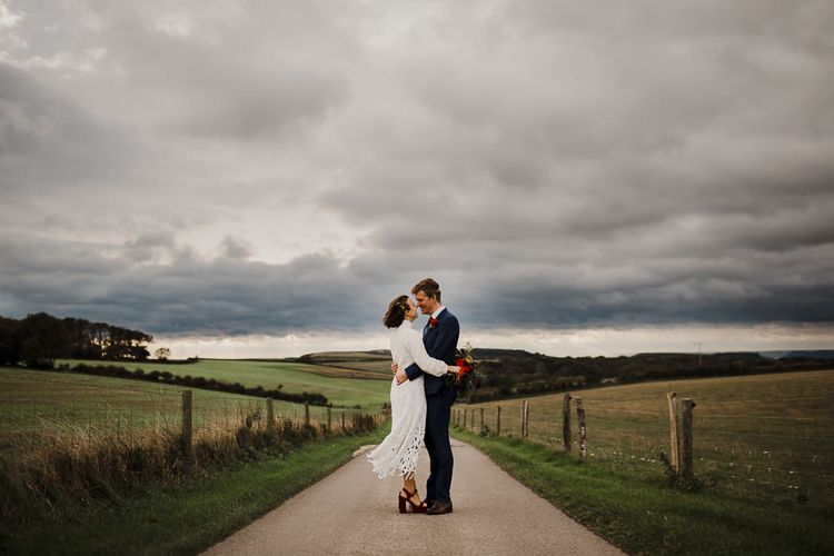 Bride in Crochet Wedding Dress and Woollen Jumper and Groom in Navy Suit Embracing Down a Country Lane