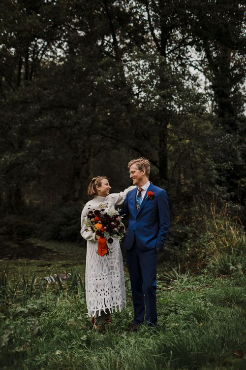 Bride in Crochet Wedding Dress and Woollen Jumper and Groom in Navy Paul Smith Suit Hugging in the Countryside