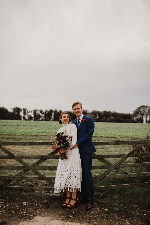 Bride in Crochet Wedding Dress and Woollen Jumper and Groom in Navy Paul Smith Suit Hugging by a Field Fence
