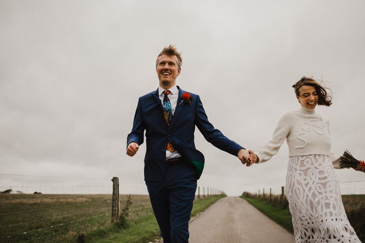 Bride in Crochet Wedding Dress and Woollen Jumper and Groom in Navy Paul Smith Suit Skipping Down a Country Lane