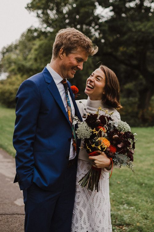 Bride in Crochet Wedding Dress and Woollen Jumper and Groom in Navy Paul Smith Suit Laughing Together