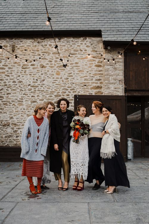 Bride in Crochet Wedding Dress and Woollen Jumper Posing with her Best Friends