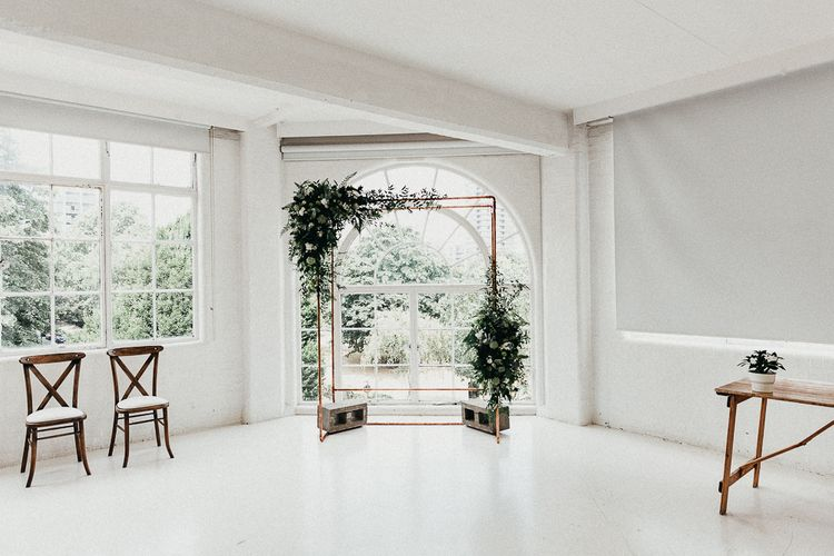 Wedding Ceremony Decor | Copper Arch with White Flowers and Foliage | Whitewashed Walls | Same Sex Wedding with Industrial Styling at Wimborne House | Marmelo Photography