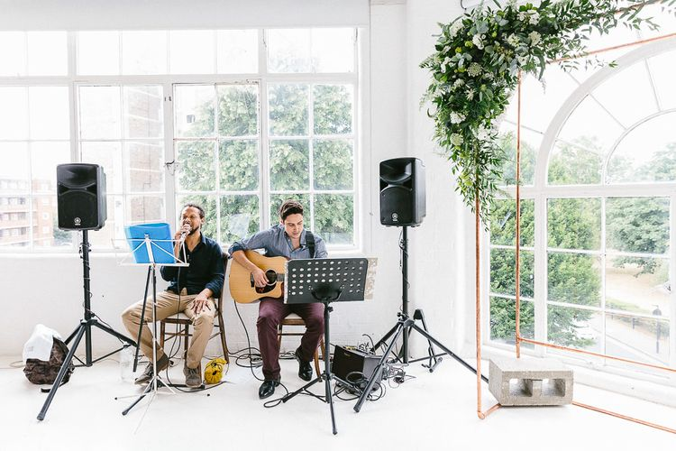 Wedding Ceremony | Acoustic Duo | Copper Arch with White Flowers and Foliage | Whitewashed Walls | Same Sex Wedding with Industrial Styling at Wimborne House | Marmelo Photography