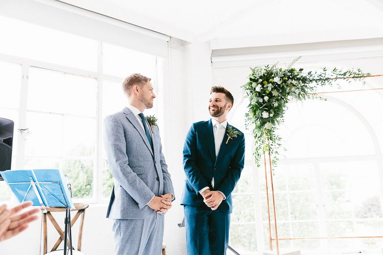Wedding Ceremony | Groom in Dark Petrol Blue Suit by Paul Smith | Groom in Light Blue Made-To-Measure Suit by Beggars Run | Copper Arch with White Flowers and Foliage | Same Sex Wedding with Industrial Styling at Wimborne House | Marmelo Photography