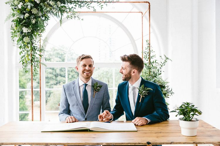 Signing of Register | Copper Arch with White Flowers and Foliage | Groom in Dark Petrol Blue Suit by Paul Smith | Groom in Light Blue Made-To-Measure Suit by Beggars Run | Same Sex Wedding with Industrial Styling at Wimborne House | Marmelo Photography