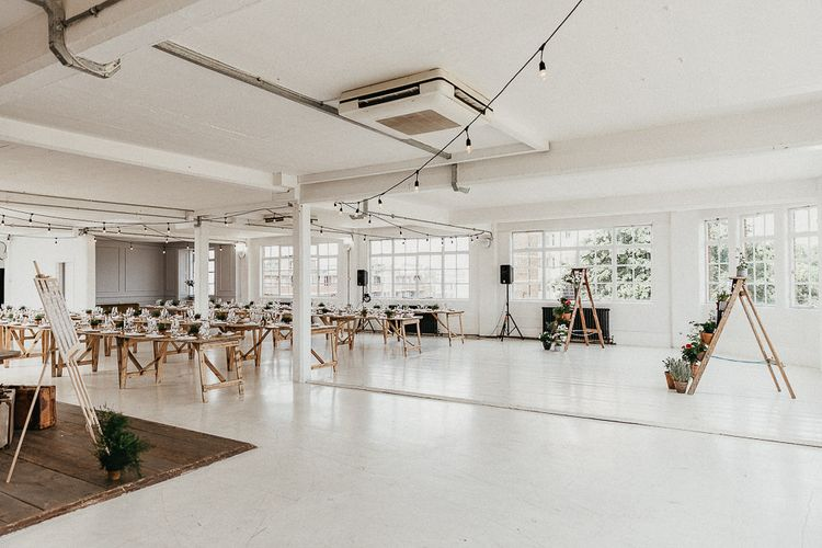 Wedding Reception Decor | Trestle Tables | Festoon Lights | Seating Plan | Windows | Whitewashed Walls | Industrial Ladder with Potted Plants | Same Sex Wedding with Industrial Styling at Wimborne House | Marmelo Photography