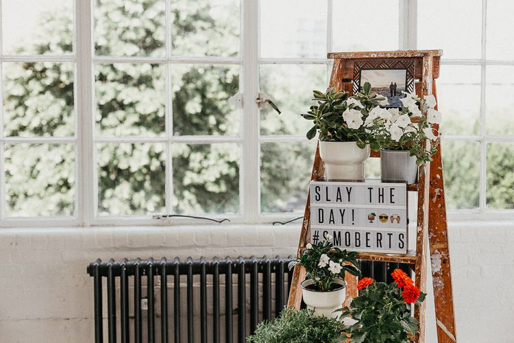 Wedding Reception Decor | Industrial Ladder with Potted Plants | Light Box | Large Warehouse Window | Same Sex Wedding with Industrial Styling at Wimborne House | Marmelo Photography