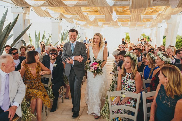 Outdoor Wedding Ceremony | Bridal Entrance in Custom Clemence Halfpenny London Bridal Gown | Brightly Coloured Destination Wedding at Masseria Potenti Wedding Venue, Puglia, South Italy | Petar Jurica Photography | Marco Odorino Film