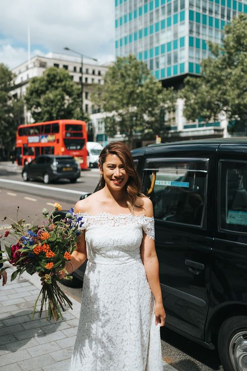 Bride in Lace Whistles Wedding Dress with High/Low Hem and Bardot Neckline | Bridal Bouquet with Bright Wild Flowers | High Street Wedding Dress for an Intimate Crouch End Pub Wedding with Bright Flowers | Miss Gen Photography