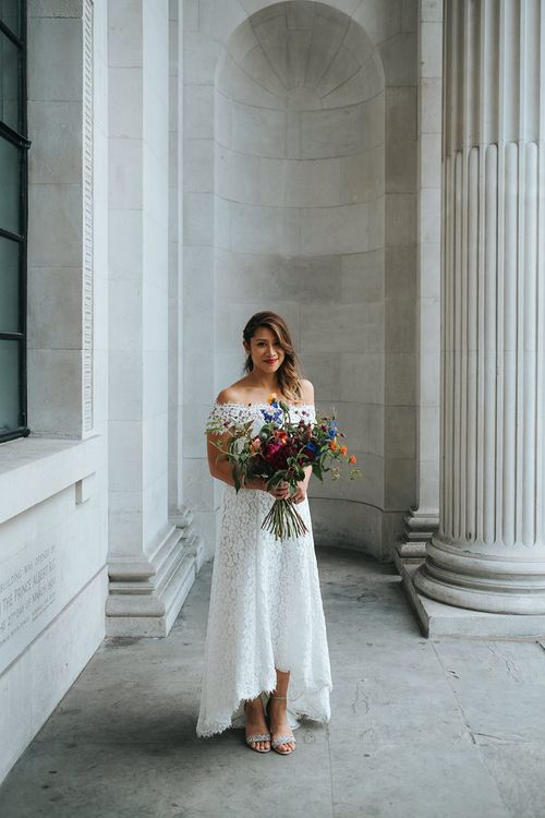 Bride in Lace Whistles Wedding Dress with High/Low Hem and Bardot Neckline | Bridal Bouquet with Bright Wild Flowers | Silver Sparkly Kurt Geiger Heels | High Street Wedding Dress for an Intimate Crouch End Pub Wedding with Bright Flowers | Miss Gen Photography