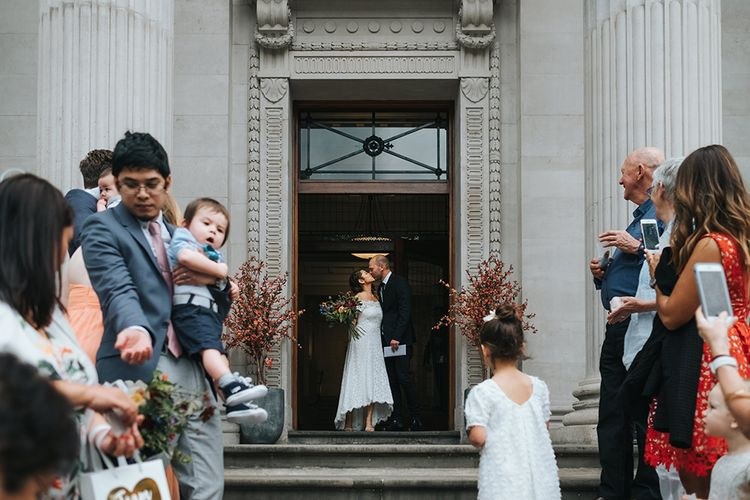 Bride in Lace Whistles Wedding Dress with High/Low Hem and Bardot Neckline | Silver Sparkly Kurt Geiger Heels | Groom in Black Reiss Jacket and Black Nudie Jeans with Church's Shoes | Bridal Bouquet with Bright Wild Flowers | Wedding Ceremony at Old Marylebone Town Hall | High Street Wedding Dress for an Intimate Crouch End Pub Wedding with Bright Flowers | Miss Gen Photography