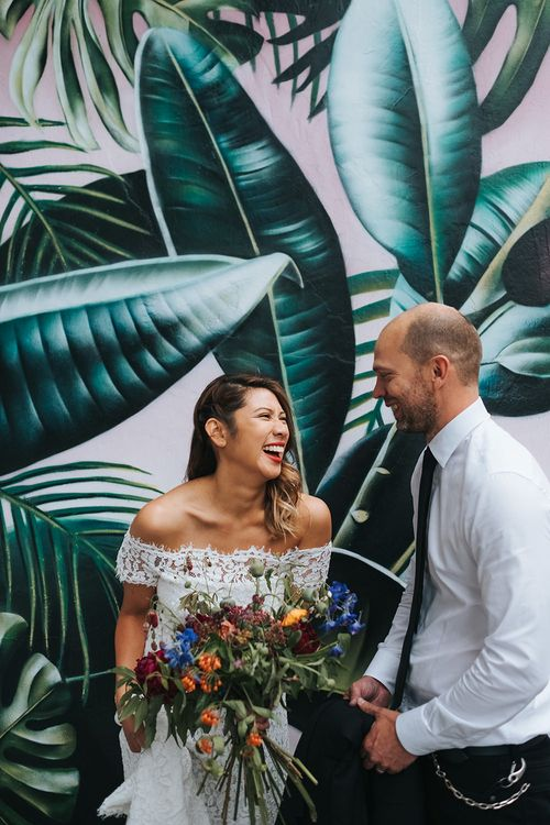 Bride in Lace Whistles Wedding Dress with High/Low Hem and Bardot Neckline | Groom in Black Reiss Jacket and Black Nudie Jeans with Church's Shoes | Bridal Bouquet with Bright Wild Flowers | High Street Wedding Dress for an Intimate Crouch End Pub Wedding with Bright Flowers | Miss Gen Photography