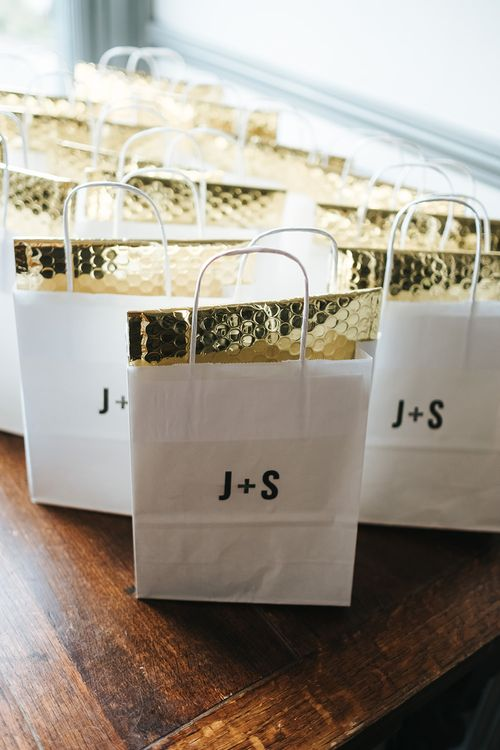 Paper Party Bags with Initials Monogram and Gold Envelopes | Victoria Stakes Pub Wedding Reception | High Street Wedding Dress for an Intimate Crouch End Pub Wedding with Bright Flowers | Miss Gen Photography