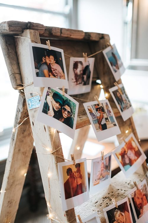 Polaroid Photos Strung on Wooden Easel with Pegs and Fairy Lights | Victoria Stakes Pub Wedding Reception | High Street Wedding Dress for an Intimate Crouch End Pub Wedding with Bright Flowers | Miss Gen Photography