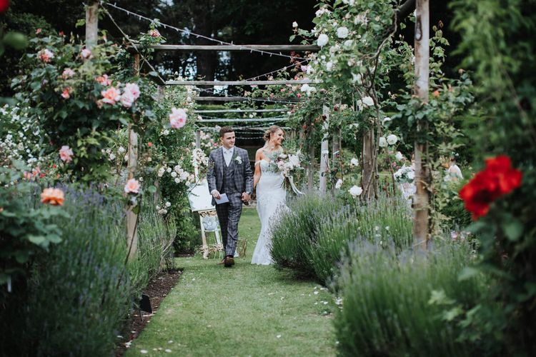 Bride And Groom Walk Through Grounds With Floral Backdrop