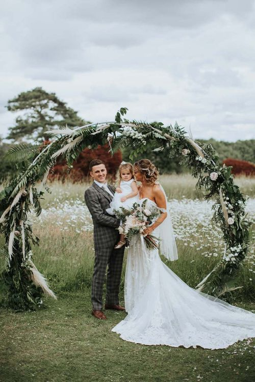 Bride and Groom With Daughter Under Moon Gate And Floral Backdrop