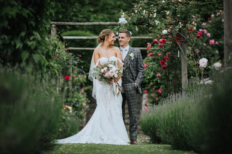 Bride and Groom Embrace Under Floral Backdrop