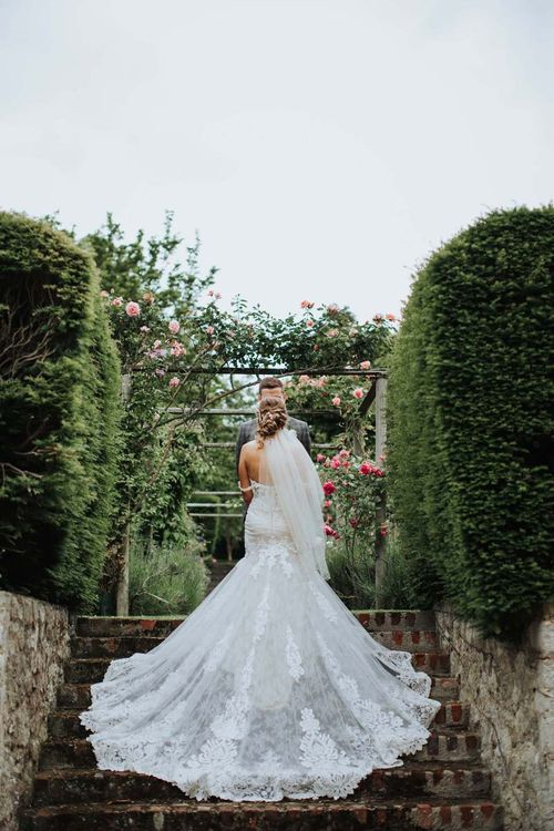 Lace Off The Shoulder Wedding Dress With Veil And Floral Backdrop