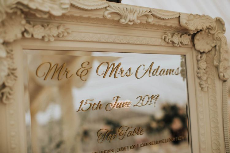 Mirrored Wedding Signs In Marquee With Floral Backdrop