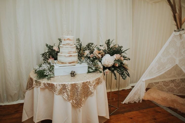 Wedding Cake Table Decorated With Pink and White Floral Backdrop