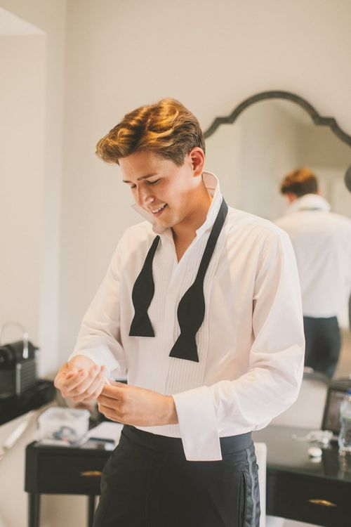 Groom Getting Ready on the Wedding Morning with a Loose Bow Tie Around His Neck