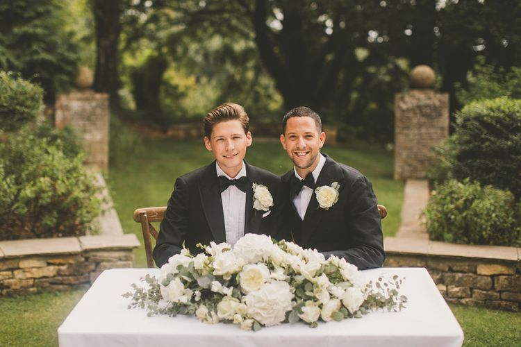 Groom and Groom Sitting at the Wedding Ceremony Table with White Floral Arrangement