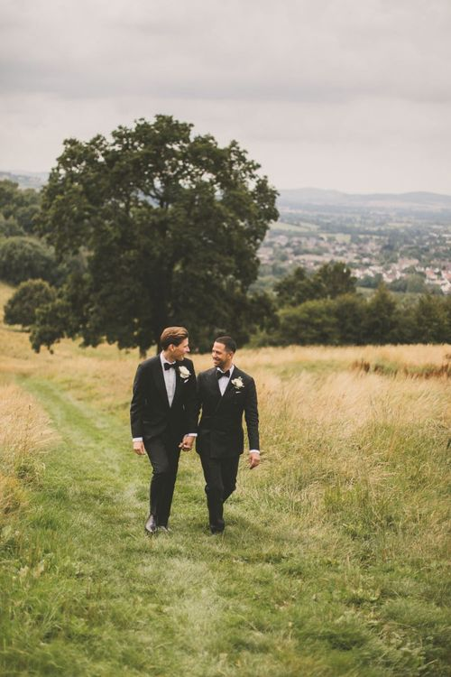 Two Grooms in Black Tie Suits Walking Through Fields