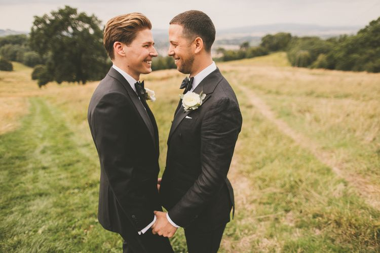 Portrait of Grooms in Tuxedos Smiling at Each Other Holding Hands in a Field