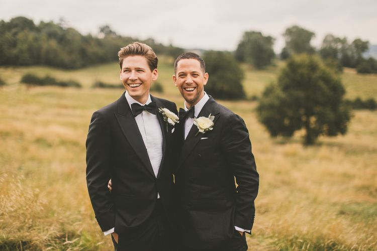 Portrait of Same Sex Couple in Black Tie Suits Smiling in a Field