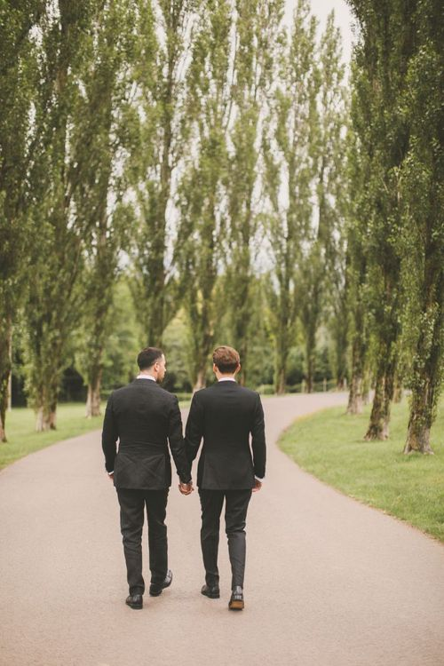 Portrait of Same Sex Couple in Black Tie Suits Holding Hands Walking Down a Country Lane
