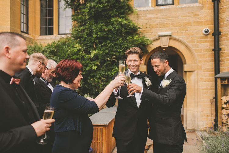 Groomsmen in Tuxedo 'Cheers' with Wedding Guests
