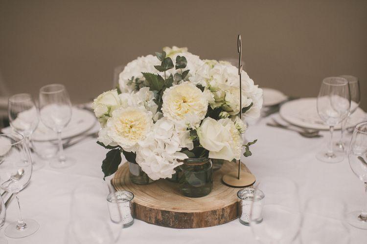 White Flower Centrepiece in Jam Jars on Wooden Tree Slice