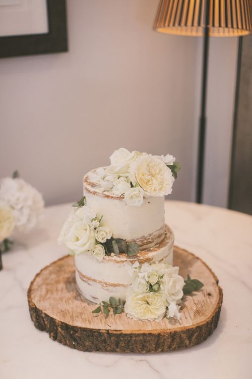 Two Tier Semi Naked Wedding Cake Decorated with White Flowers on Wooden Tree Slice Cake Stand