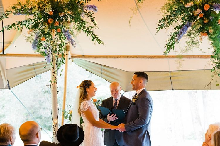 Wedding Ceremony | Exchanging Vows | Bride in Laced KatyaKatya Wedding Dress with Cap Sleeves and Ribbon Belt | Groom in Blue T.M Lewin Suit with Navy Hawkes Bespoke Outfitters Waistcoat | Arch of Flowers | Lace KatyaKatya Dress for Tipi Wedding at Fforest Farm | Claudia Rose Carter Photography