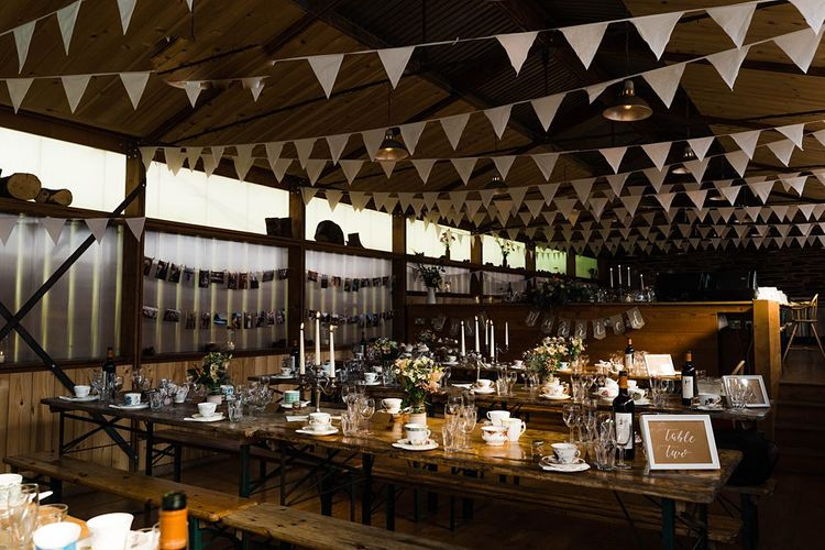 Wedding Reception Decor | On Site Pub at Fforest Farm | Long Wooden Tables and Benches | White Bunting | Flowers in Jam Jars | Tea Cups and Saucers | Candlesticks | Tapered Candles | Lace KatyaKatya Dress for Tipi Wedding at Fforest Farm | Claudia Rose Carter Photography