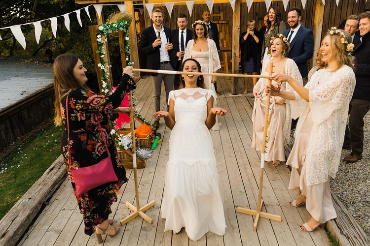 Wedding Reception Entertainment | Limbo | Bride in Laced KatyaKatya Wedding Dress with Cap Sleeves and Ribbon Belt | Bridesmaids in Dusty Pink ASOS Dresses  and White ASOS Kaftans | Flower Crowns | Lace KatyaKatya Dress for Tipi Wedding at Fforest Farm | Claudia Rose Carter Photography