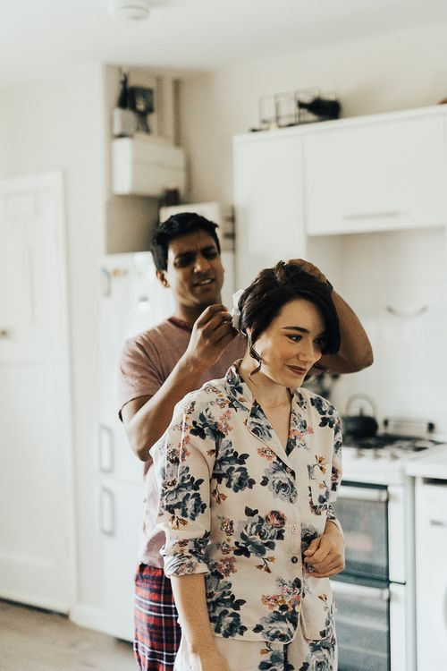 Groom helping his bride with her hair on the wedding morning