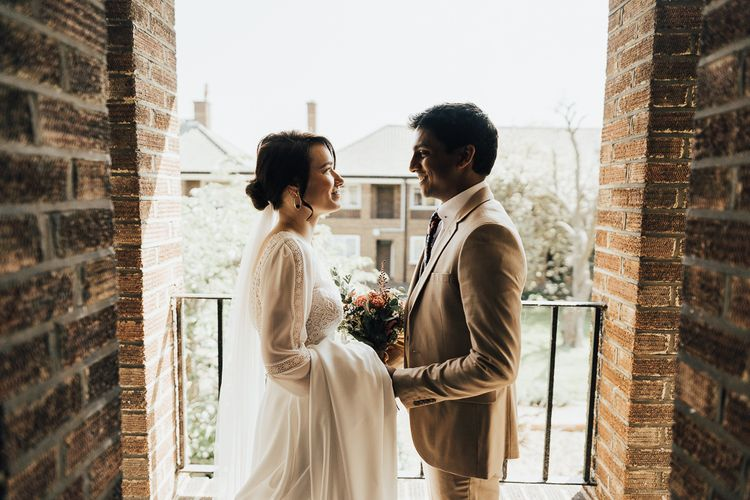 Bride in Rosa Clara wedding dress and Groom in beige suit on wedding morning