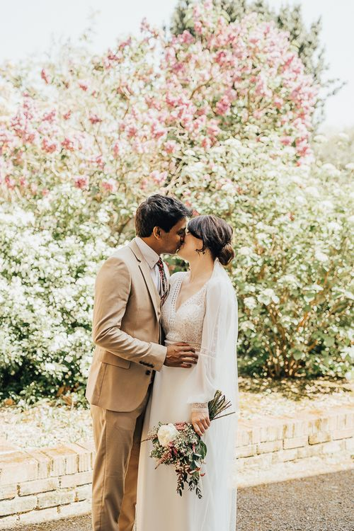 Bride and groom kissing in front of blossom tree