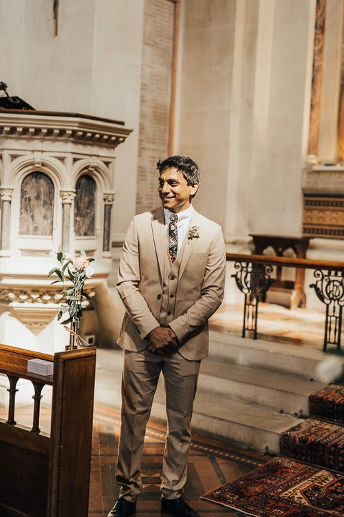 Groom in beige wedding suit with floral tie standing at the altar