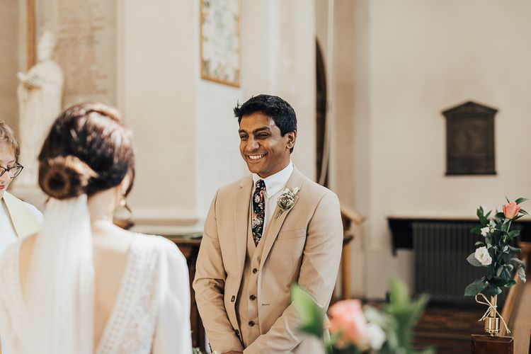 Groom in cream three-piece suit with floral tie smiling during wedding ceremony