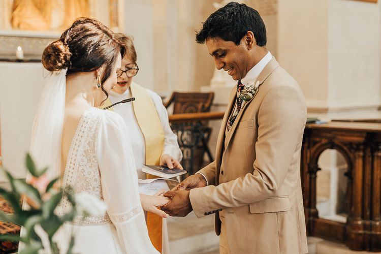 Groom in beige suit putting on his brides wedding ring