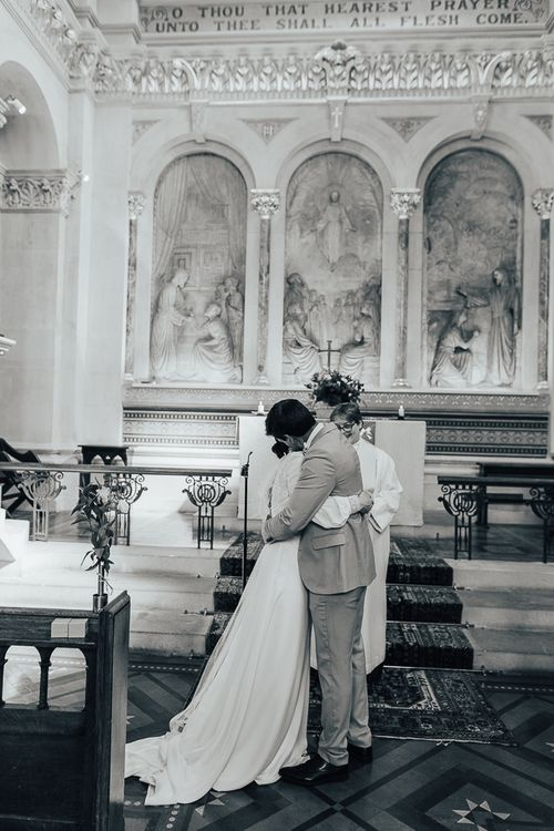 black and white portrait on bride and groom embracing  at the altar