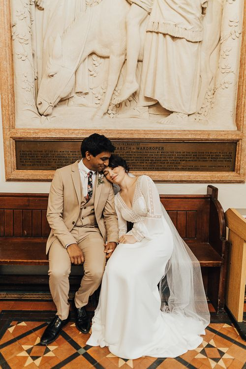 Bride in Rosa Clara wedding dress with long sleeves and groom in beige suit sitting on a wedding pew