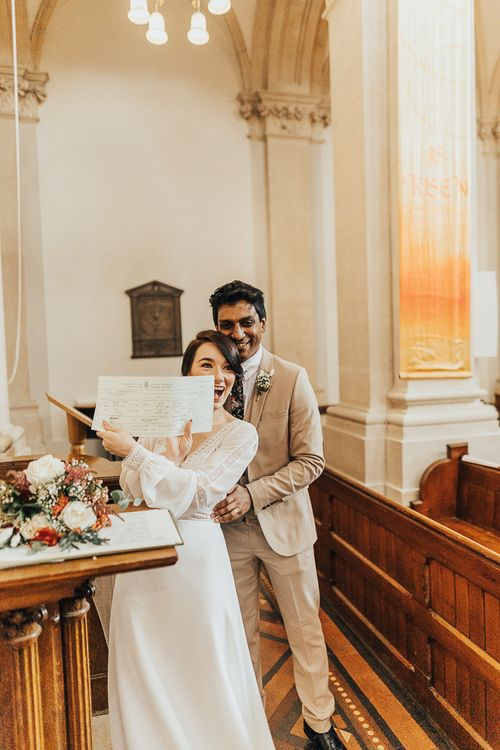 NHS nurse and doctor show their marriage certificate