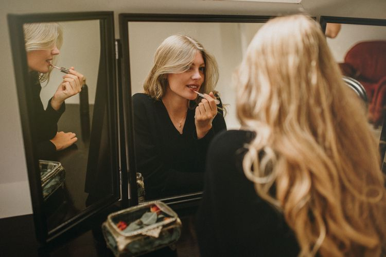 Beautiful Bride with Long Blonde Hair Putting on Her Wedding Makeup