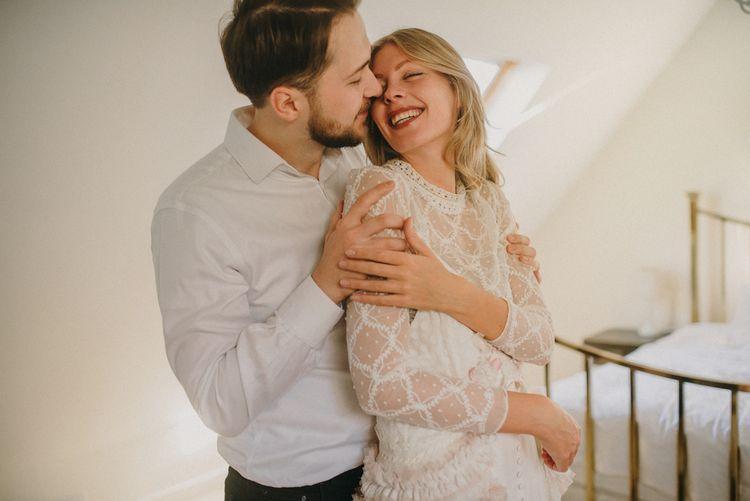 Groom in White Shirt Embracing His Boho Bride in a Sara Lage Wedding Dress