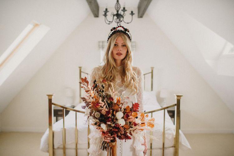 Boho Bride in Sara Lage Wedding Dress  and Verbena Madrid Headdress Holding a Dried Flower Bouquet